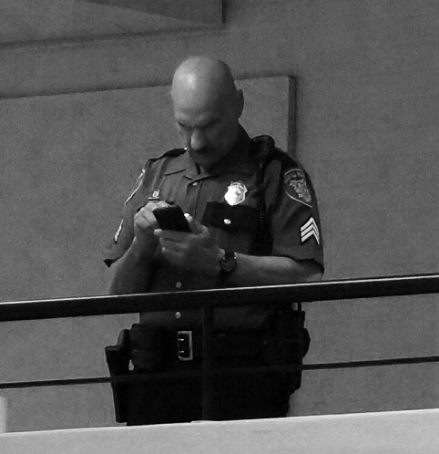 Most of the time, the cop on duty was on his cell phone.